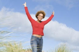 Image of woman with hands in the air in a victory pose